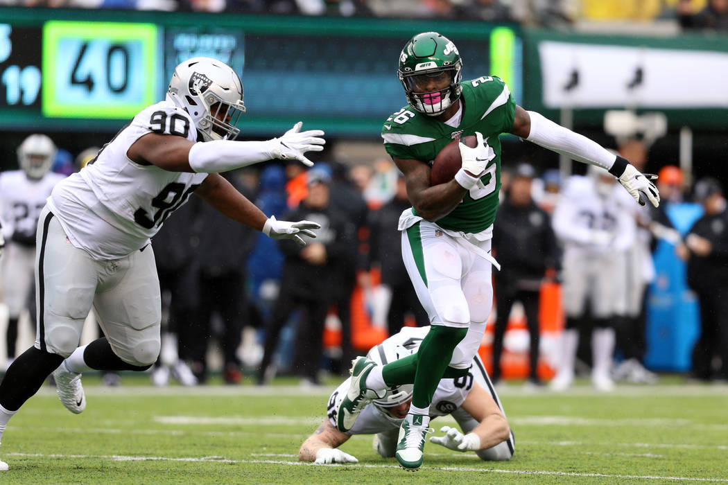 New York Jets running back Le'Veon Bell (26) sheds a tackle from Oakland Raiders defensive end ...