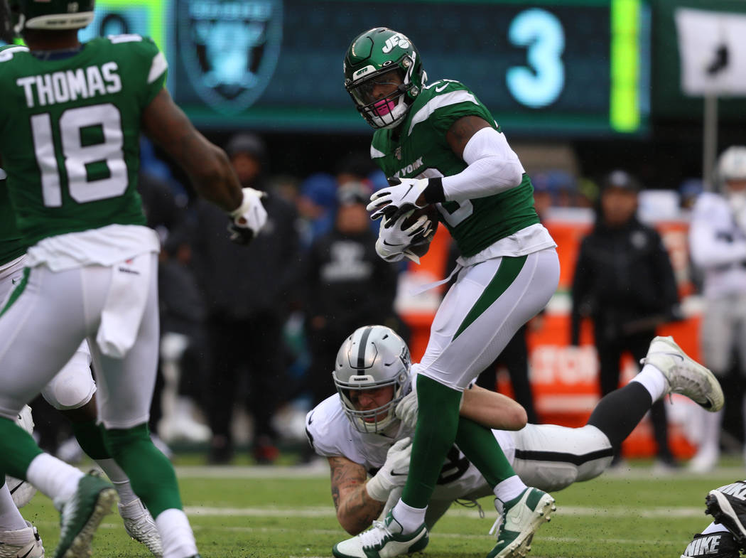 Oakland Raiders defensive end Maxx Crosby (98) can't tackle New York Jets running back Le'Veon ...