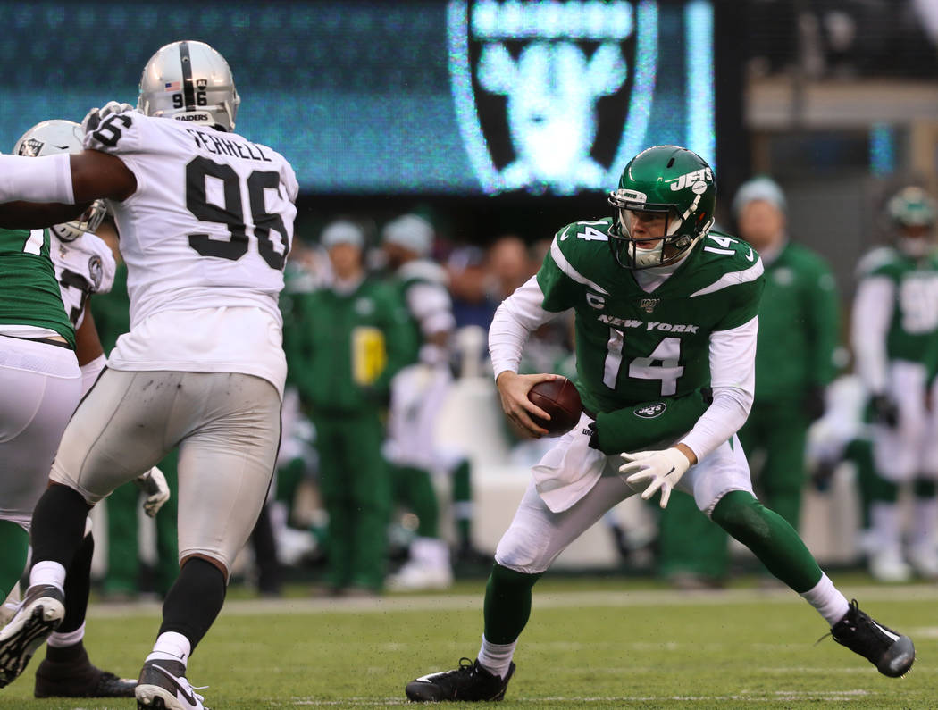 New York Jets quarterback Sam Darnold (14) scrambles with the football as Oakland Raiders defen ...