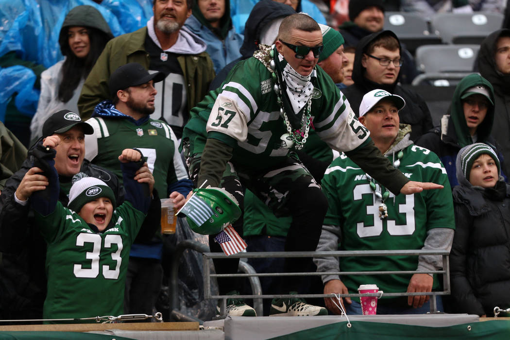 A New York Jets fan stand on the edge of the stands during the first half of an NFL game agains ...