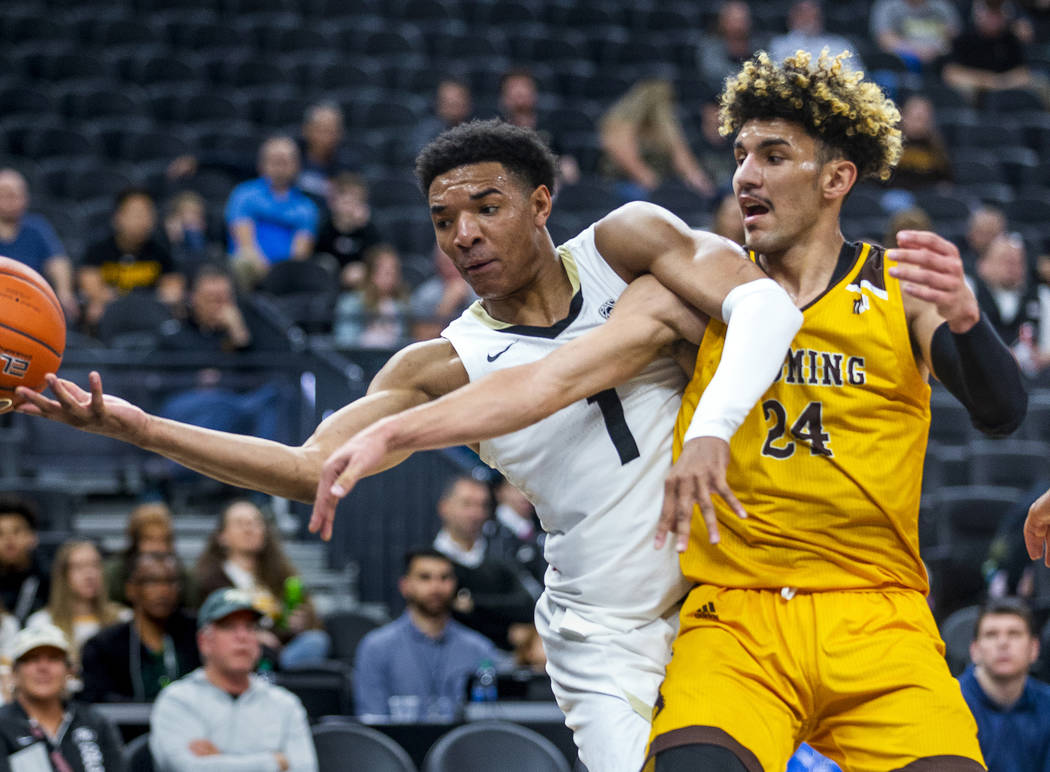 Colorado guard Tyler Bey (1, left) gets a hand on a loose ball with Wyoming guard Hunter Maldon ...