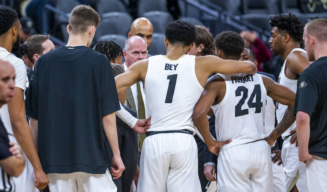 Colorado guard Tyler Bey (1) gathers with teammates for a timeout versus Wyoming during the fir ...