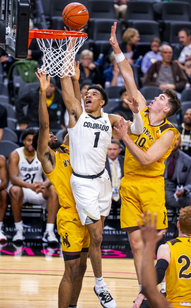 Colorado guard Tyler Bey (1, center) elevates for a shot between Wyoming forward Trevon Taylor ...