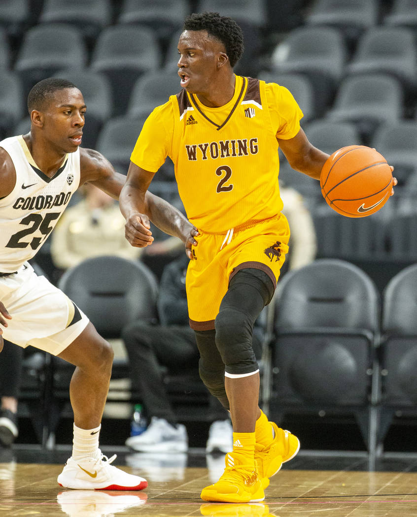 Wyoming guard A.J. Banks (2, right) looks to pass versus Colorado guard McKinley Wright IV (25) ...