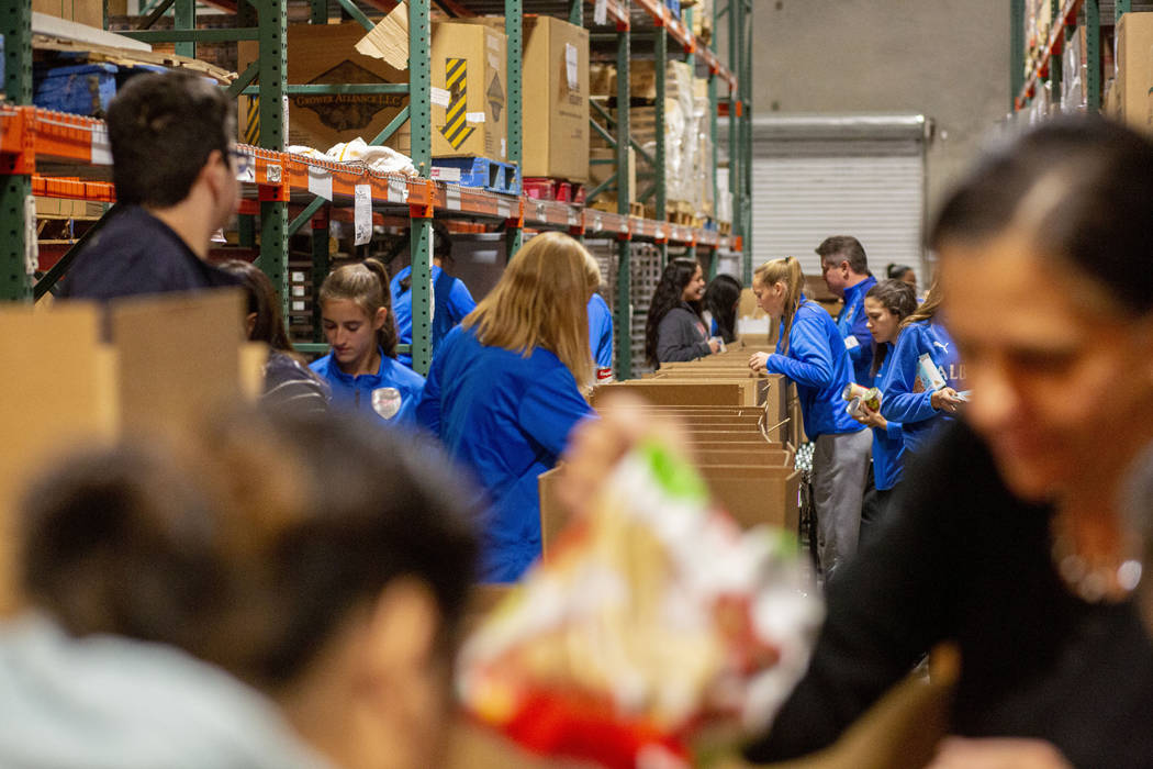 The Las Vegas Albion Soccer Club pack assorted foods in preparation for Thanksgiving at Three S ...