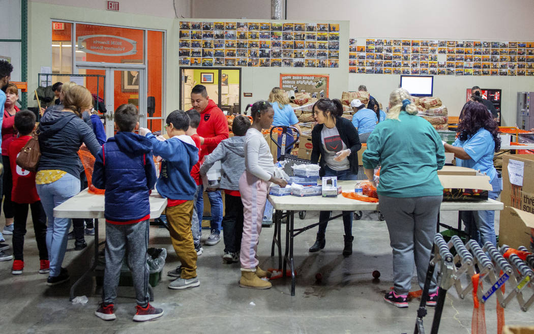 Volunteers and family members from Diamond Resorts and Las Vegas United Soccer Club pack fresh ...