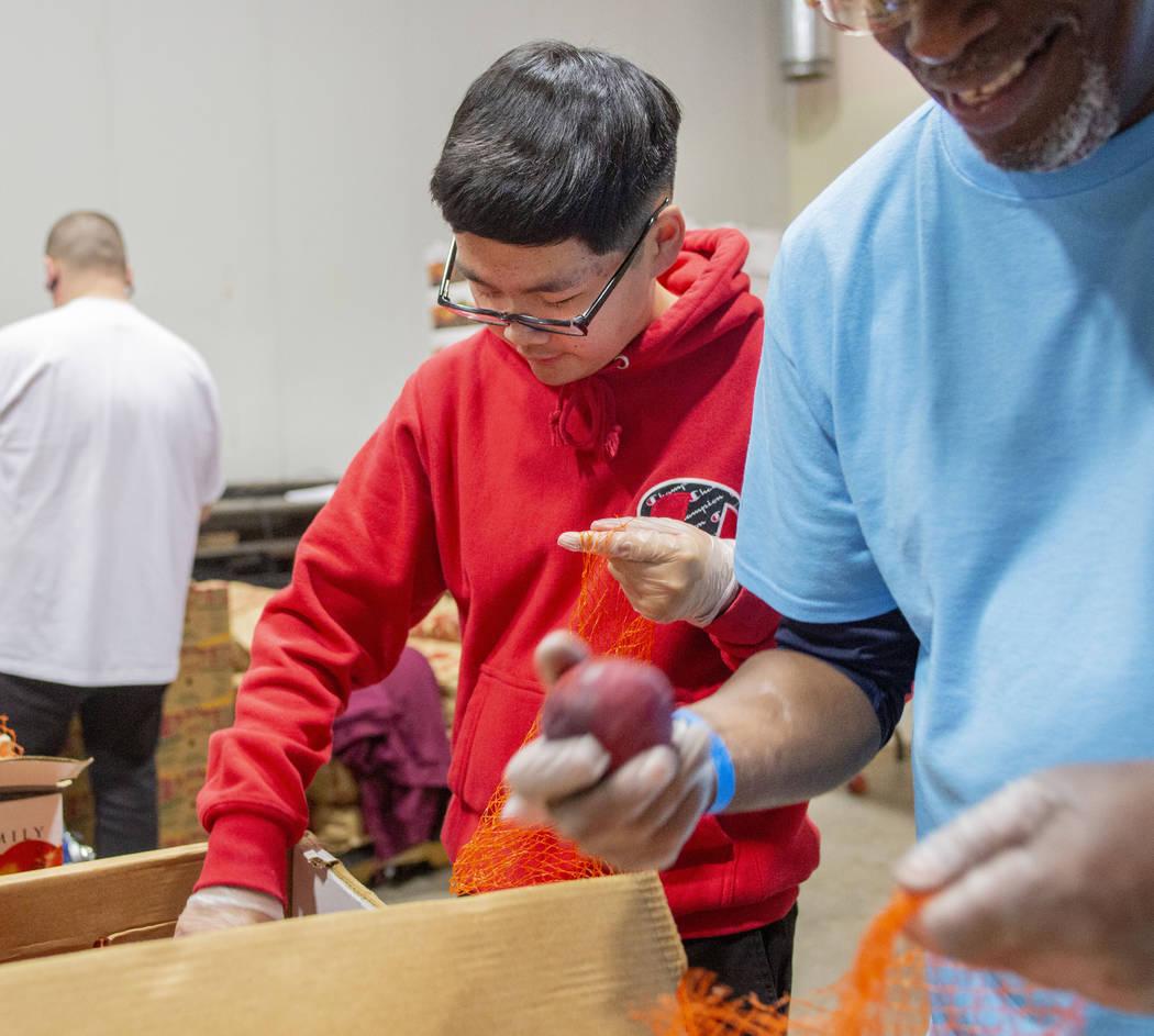 Kai Tran, 12, North Las Vegas, packs fresh produce with a volunteer team from Diamond Resorts a ...