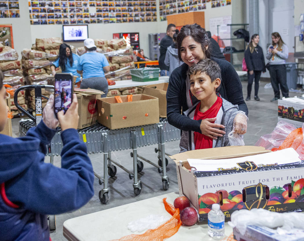 Volunteers with Vegas United Soccer Club Michelle Kannya, left, and Joah Kannya, 10, take a pho ...