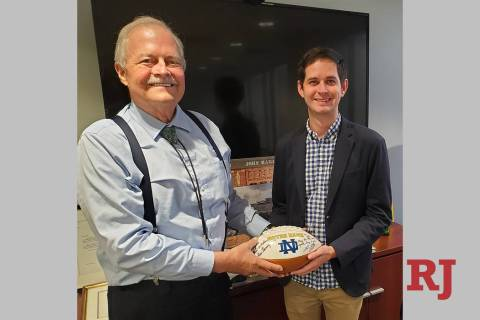 Las Vegas attorneys John Mowbray and son Tyler are shown with an autographed Notre Dame footbal ...