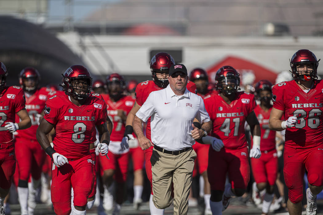 UNLV Rebels head coach Tony Sanchez leads his team on to the field before the start of their NC ...