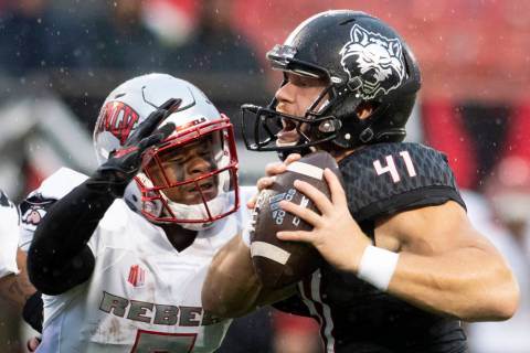 Arkansas State punter Cody Grace (41) handles the ball as UNLV defensive back Jericho Flowers ( ...