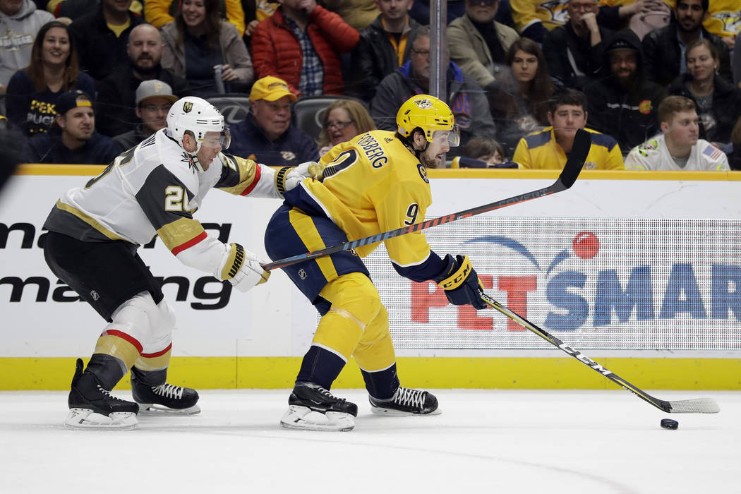 Nashville Predators left wing Filip Forsberg (9), of Sweden, is defended by Vegas Golden Knight ...