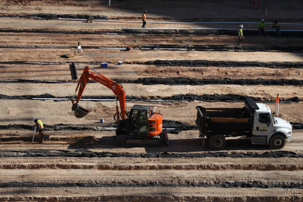 Workers on the field level of the Raiders Allegiant Stadium construction site in Las Vegas, Mon ...