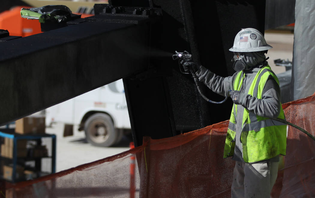 A worker paints a piece of structure of the Raiders Allegiant Stadium in Las Vegas, Monday, Nov ...