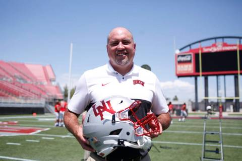 UNLV football head coach Tony Sanchez holds a unique helmet that will be worn by the players on ...