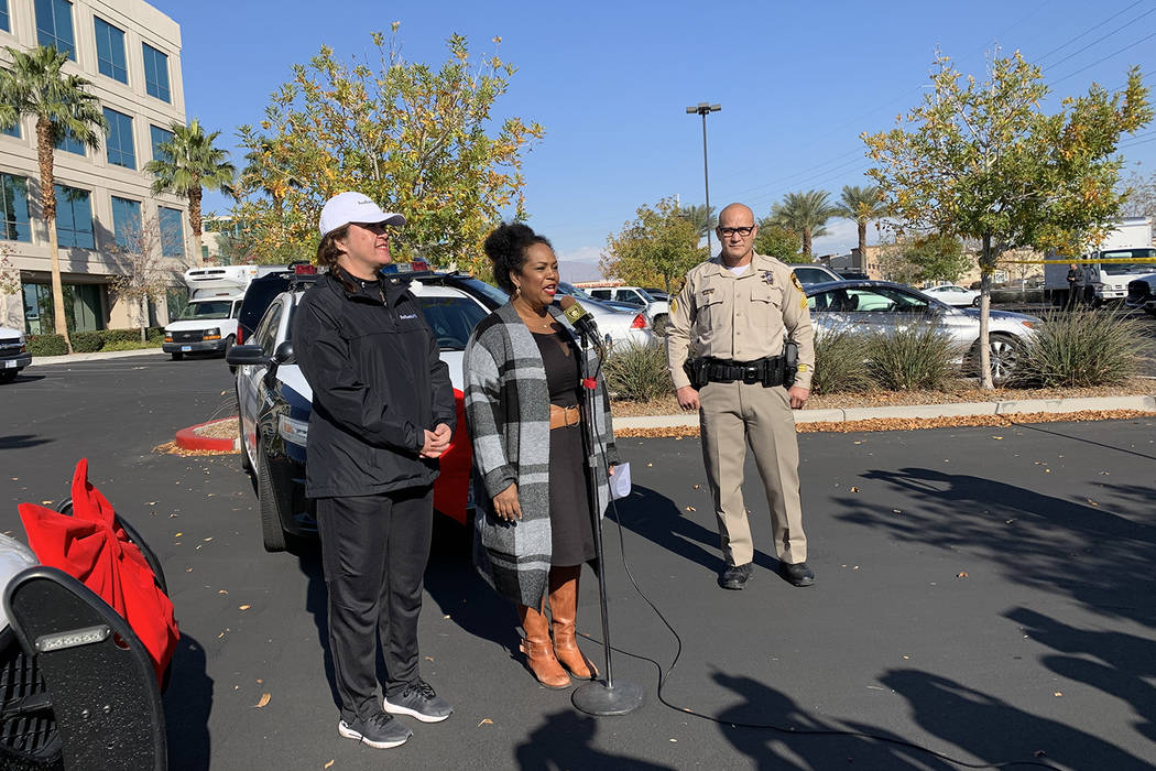Latoya Holman, director of community outreach with the LVMPD Foundation, center, said officers ...