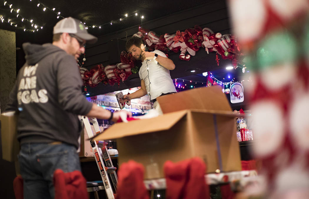 Garrett Pattiani, center, co-owner of Bright Light Holiday Company, works to hang lights at the ...