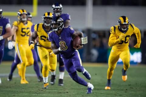 Baltimore Ravens quarterback Lamar Jackson runs against the Los Angeles Rams during the first h ...