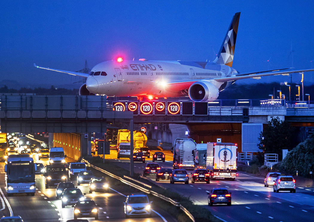 FILE - In this Friday, Sept. 20, 2019 an aircraft crosses a bridge over a highway the airport i ...