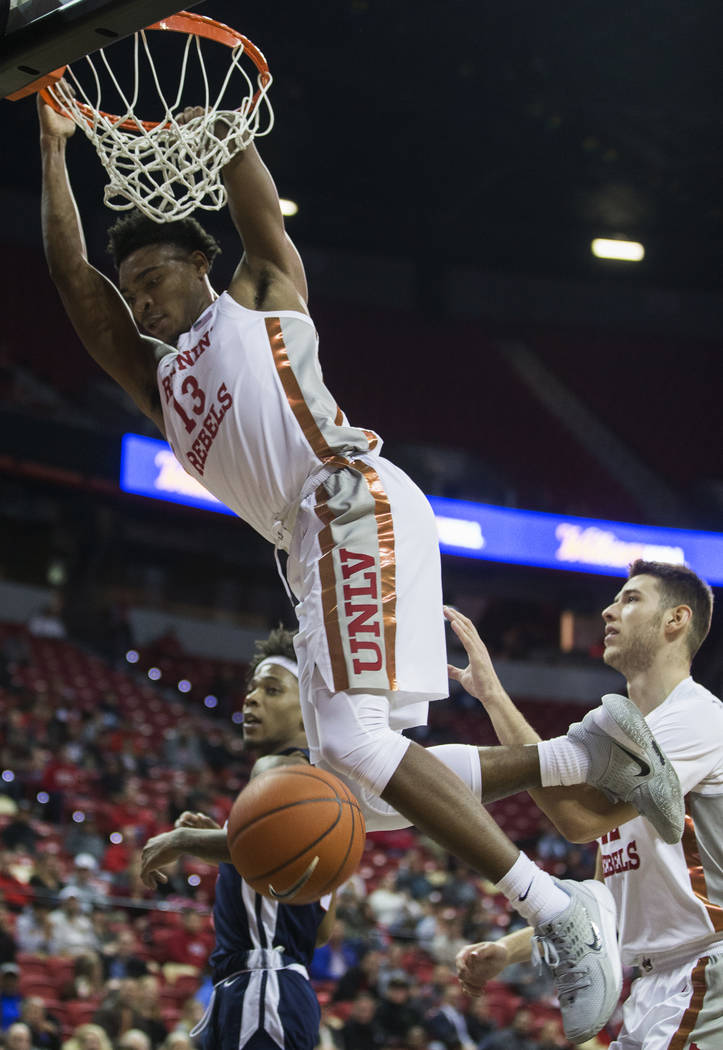 UNLV Rebels guard Bryce Hamilton (13) dunks over Jackson State Tigers guard Venjie Wallis (0) i ...