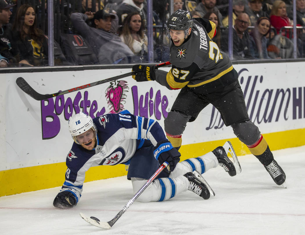 Winnipeg Jets center Bryan Little (18) goes to he ice while battling for the puck with Vegas Go ...
