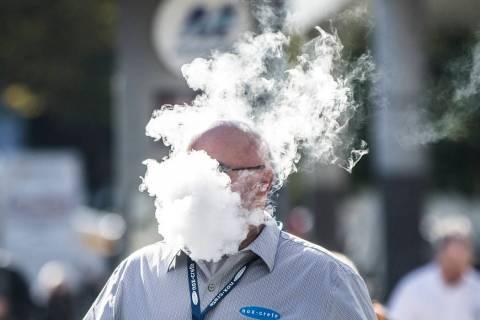 In this Jan. 23, 2019, file photo, Derick Rainey takes a vape break outside the Las Vegas Conve ...