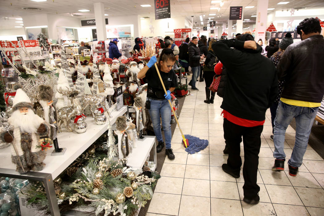 Imelda Alvarez keeps the floor dry as wet shoppers look for early Black Friday deals at JCPenny ...