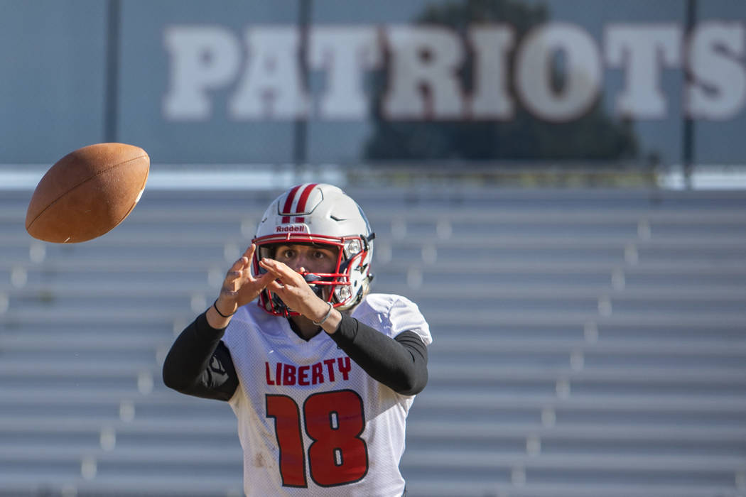 Liberty's quarterback Daniel Britt (18) is about to catch the ball during practice on Tuesday, ...