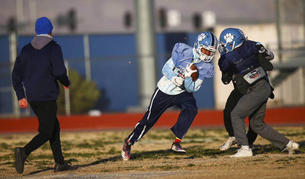 Centennial's Giovanni Monroe runs the ball during football practice at Centennial High School i ...