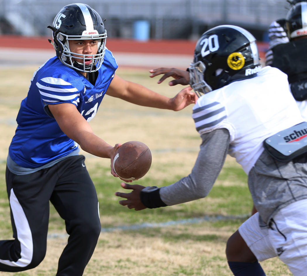 Desert Pines' Rjay Tagataese (15) hands off the ball to DeAvonte McGee (20) for a run during a ...
