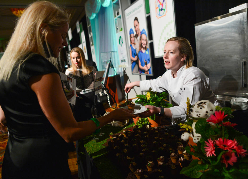 Chef Nicole Erle, right, from CUT by Wolfgang Puck, hands one of her tropical fruit dirt cups t ...