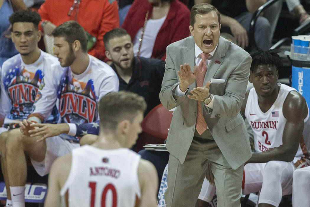 UNLV Rebels head coach T.J. Otzelberger, top/right, directs his team during their NCAA basketba ...