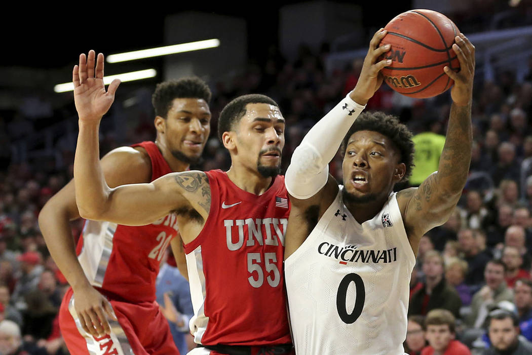 Cincinnati guard Chris McNeal (0) drives to the basket as UNLV guard Elijah Mitrou-Long (55) de ...