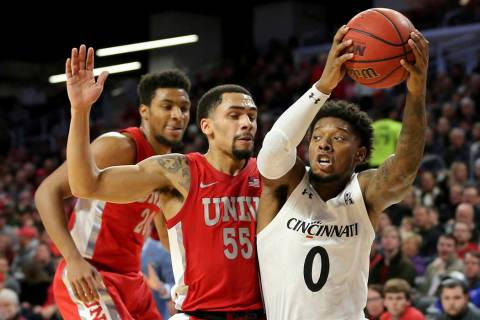 Cincinnati guard Chris McNeal (0) drives to the basket as UNLV guard Elijah Mitrou-Long (55) de ...