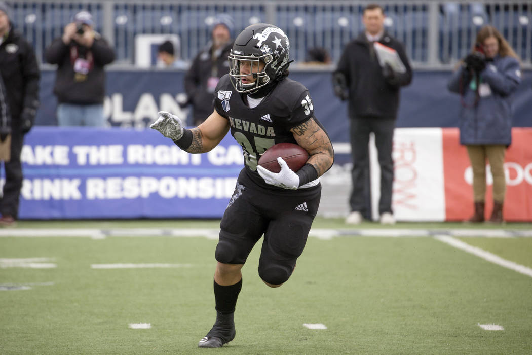 Nevada running back Toa Taua (35) runs against UNLV in the first half of an NCAA college footba ...