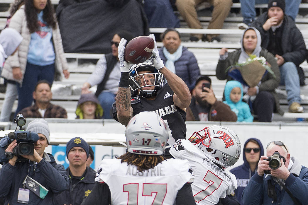 Nevada wide receiver Elijah Cooks, top, goes up for a pass over UNLV's Jericho Flowers (7) in t ...