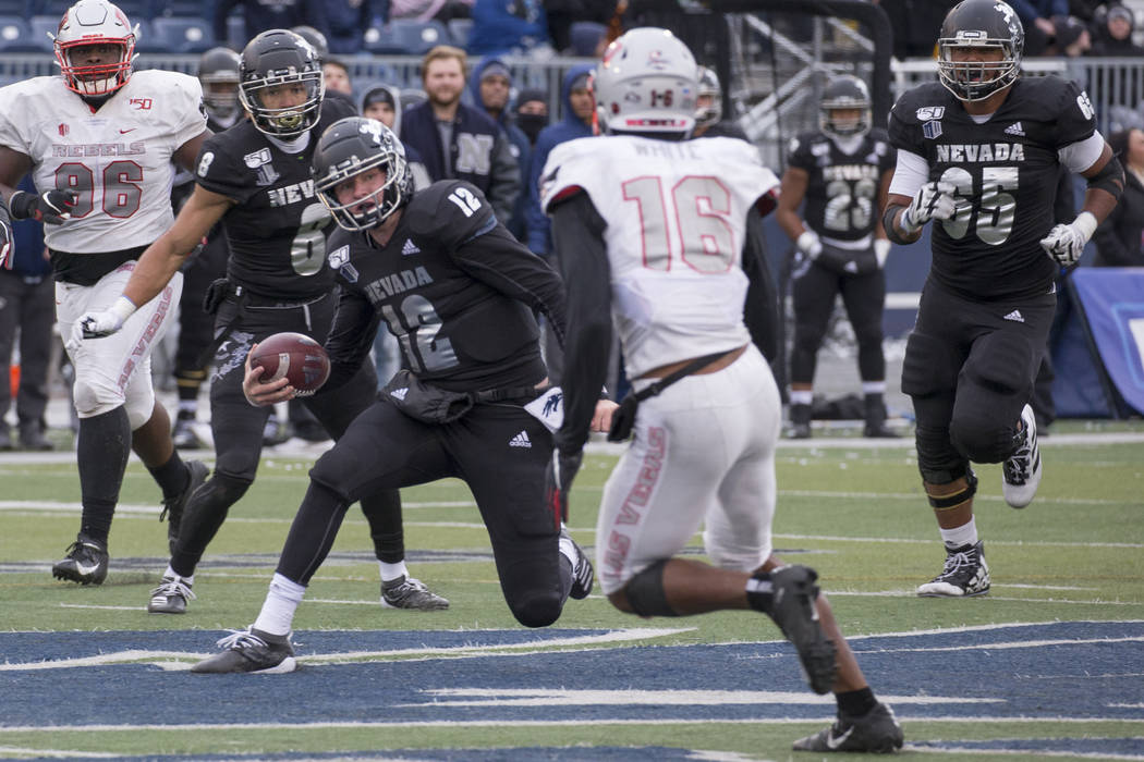 Nevada quarterback Carson Strong (12) cuts back as UNLV linebacker Javin White (16) makes a pla ...