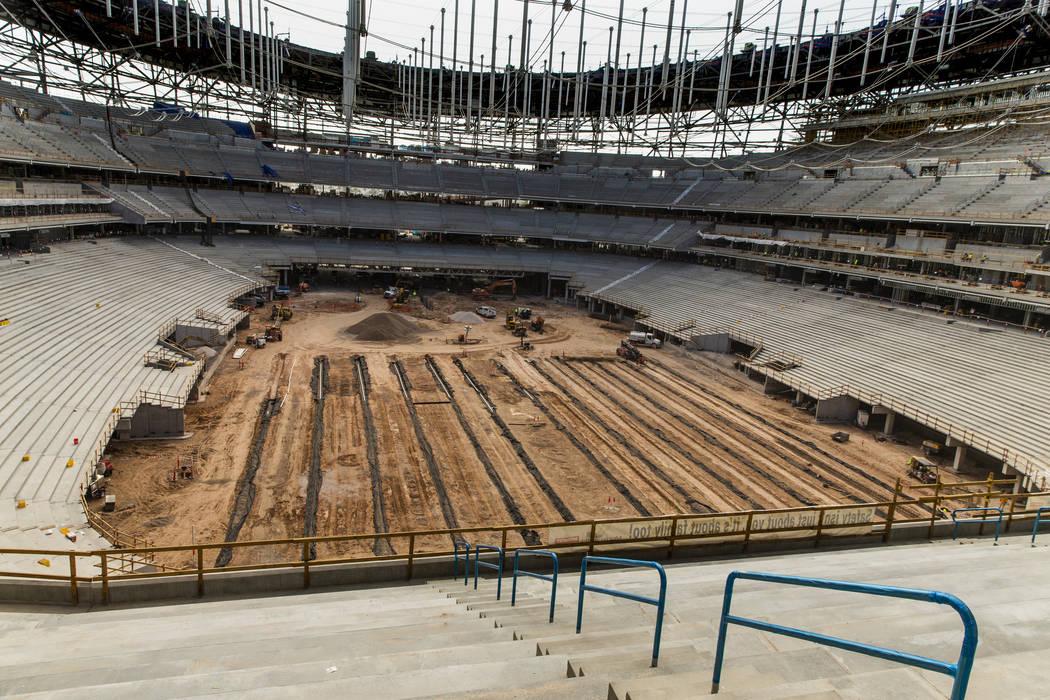 Crews continue on the arena floor during a tour of the Raiders Allegiant Stadium construction s ...