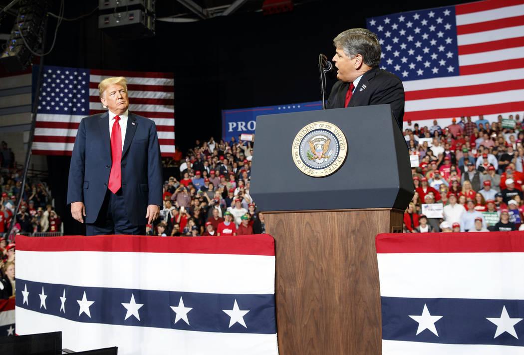 President Donald Trump listens Fox News' Sean Hannity speak. (AP Photo/Carolyn Kaster)