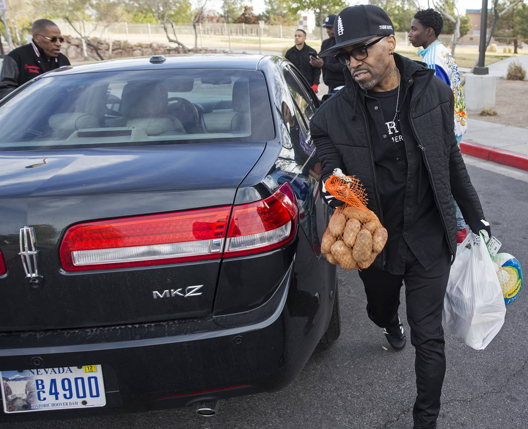 Singer/songwriter Teddy Riley, right, delivers Thanksgiving dinners to a car during an event or ...