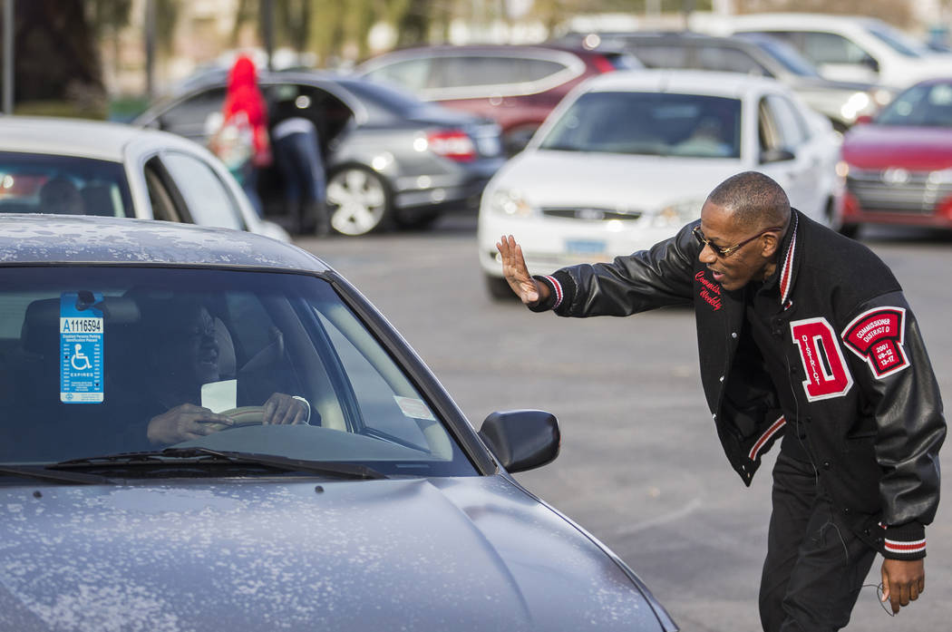 Clark County Commission Vice Chairman Lawrence Weekly, right, greets vehicles as they arrive at ...