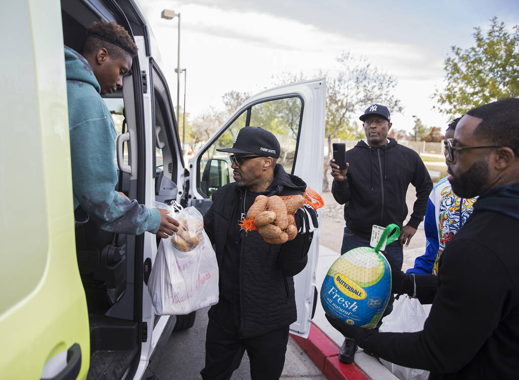Sincere Basped, left, Teddy Riley and Will Roundtree load Thanksgiving dinners onto a bus durin ...