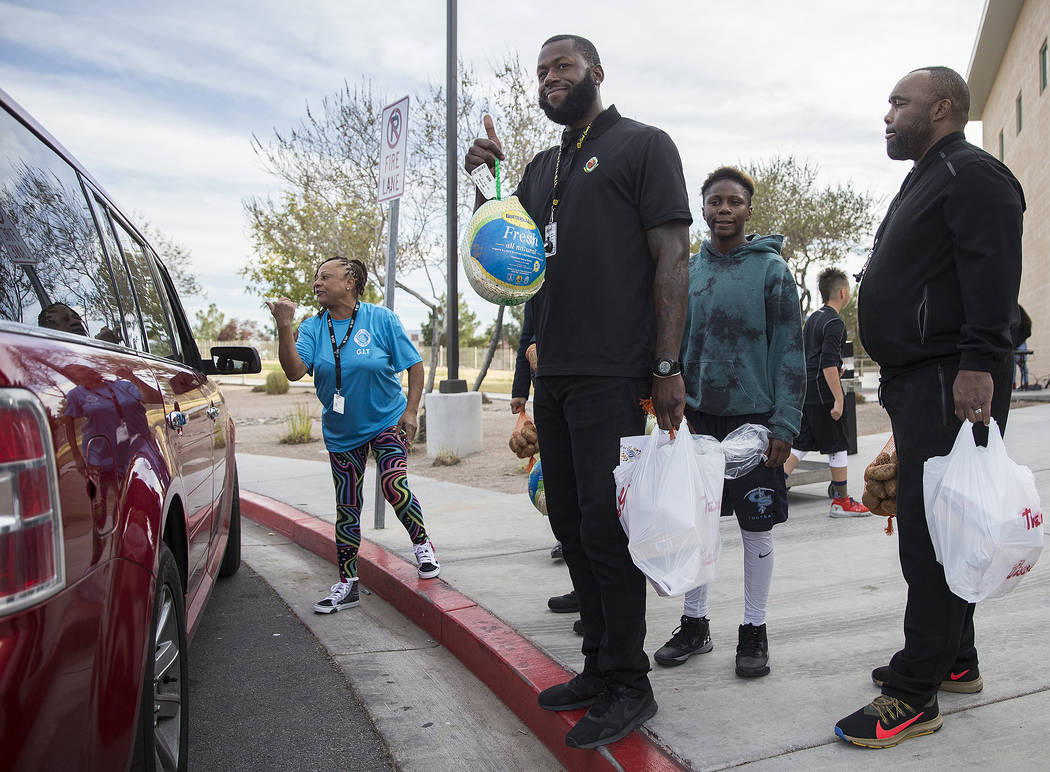 Gene Stokes, left, Luke James, Sincere Basped and Cedric Williams wait to load cars with Thanks ...