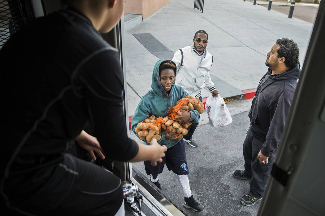 Sincere Basped, second from left, and Mark Smitty deliver Thanksgiving dinners to a bus during ...
