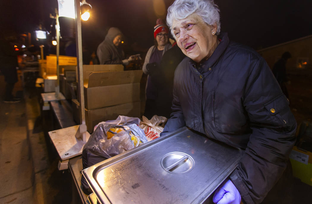 Volunteer Christine Ruland helps to serve some hot dinner to those in need gathered for the Giv ...