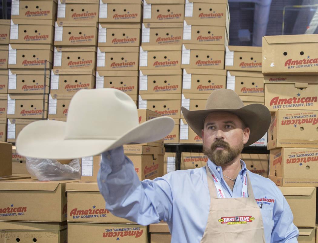 Tye Chesser, a la derecha, un representante de ventas de American Hat Company, ayuda a un clien ...