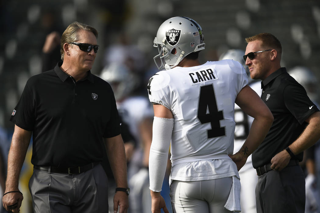 Oakland Raiders quarterback Derek Carr (4) talks with Oakland Raiders head coach Jack Del Rio, ...