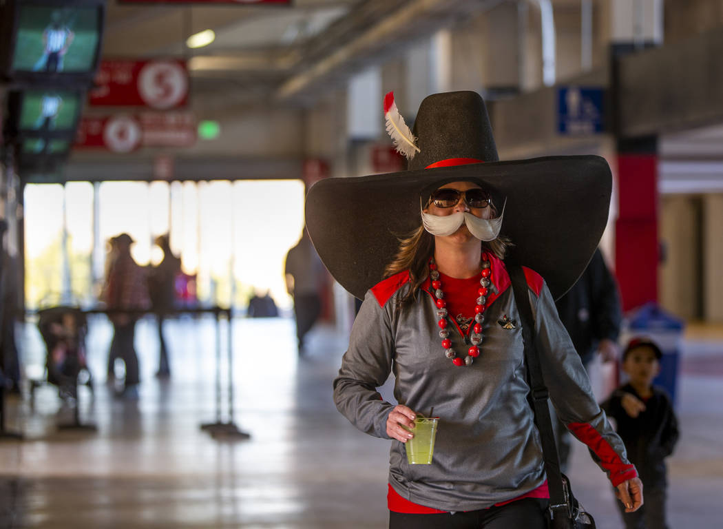Kim Arrasate in a Hey Reb costume makes her way through the concourse after purchasing a drink ...