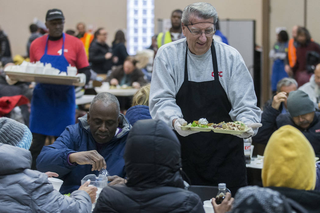 Volunteer Alan Kotwica, top/right, serves a tray of food during the Las Vegas Rescue Mission's ...