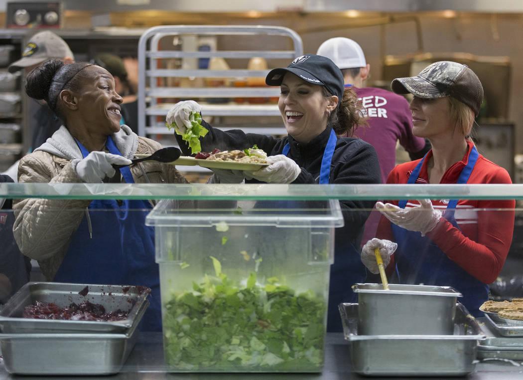 Volunteers Yolanda Grimes, left, Beth Louton and Jamie Almasi prepare trays of food during the ...